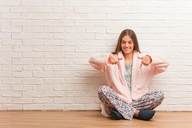 Tragender pyjama der jungen frau, der auf die unterseite mit den fingern zeigt