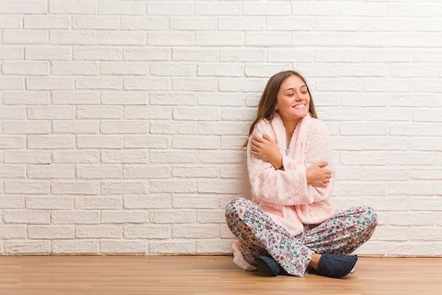 Tragender pyjama der jungen frau, der eine umarmung gibt