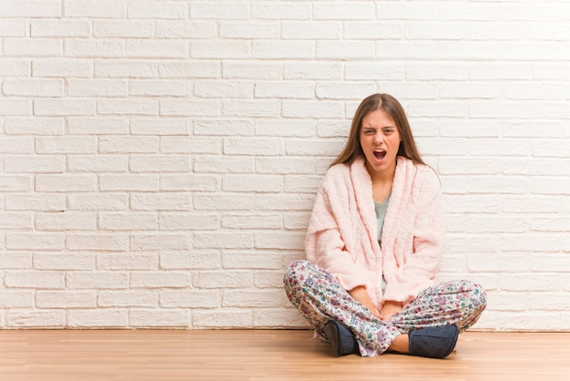 Tragender pyjama der jungen frau, der sehr verärgert und konkurrenzfähig schreit