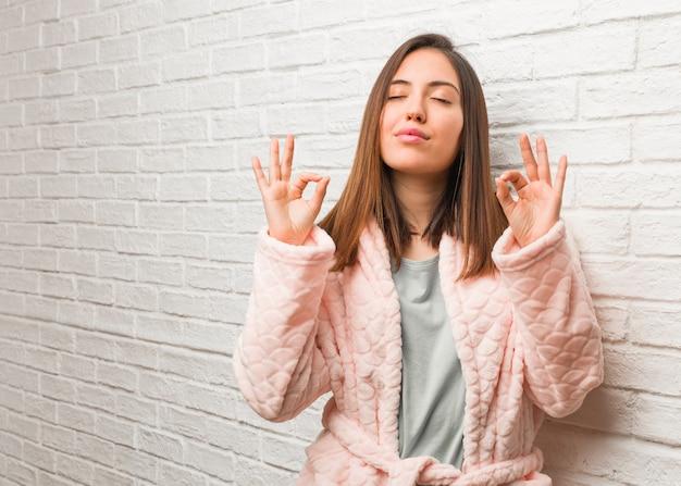 Tragender pyjama der jungen frau, der yoga durchführt
