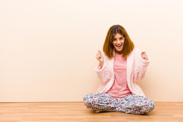 Tragender pyjama der jungen frau, der zu hause sitzt und entsetzt, aufgeregt und glücklich sich fühlt, erfolg lacht und feiert und wow sagt!