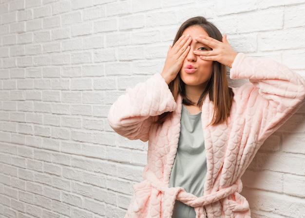 Tragender pyjama der jungen frau fühlt sich besorgt und erschrocken