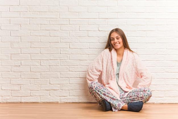 Tragender pyjama der jungen frau mit den händen auf hüften
