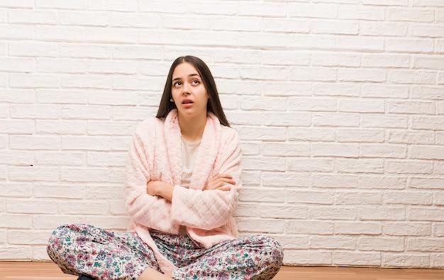 Tragender pyjama der jungen frau müde und gelangweilt