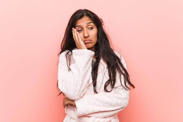 Tragender pyjama der jungen indischen frau, der gelangweilt, ermüdet ist und einen entspannungstag benötigt.
