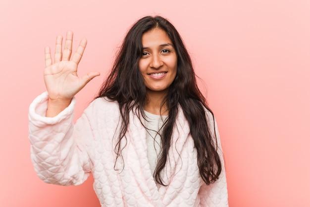 Tragender pyjama der jungen indischen frau, der nette darstellende nr. fünf mit den fingern lächelt.