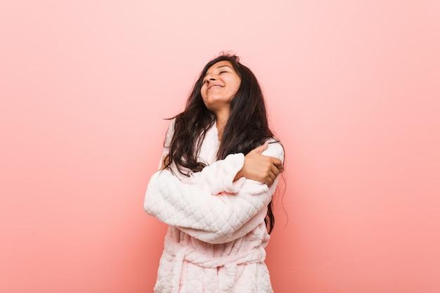 Tragender pyjama der jungen indischen frau umarmt sich und lächelt sorglos und glücklich.