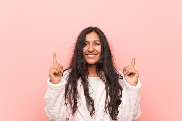 Tragender pyjama der jungen indischen frau zeigt mit beiden vorderfingern an, die sich einen freien raum zeigen.