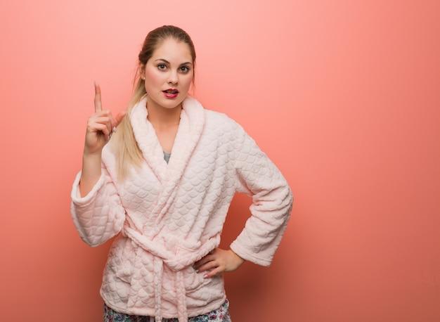 Tragender pyjama der jungen russischen frau, der eine idee, inspirationskonzept hat