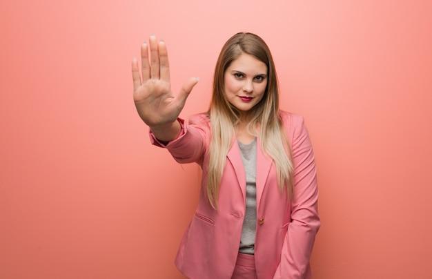 Tragender pyjama der jungen russischen frau, der hand in front einsetzt