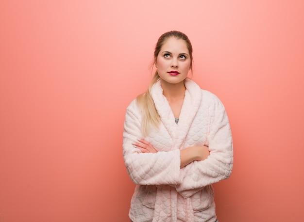 Tragender pyjama der jungen russischen frau müde und gelangweilt