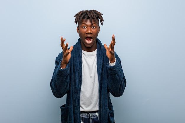Tragender pyjama des jungen afrikanischen schwarzen mannes, der einen sieg oder einen erfolg feiert