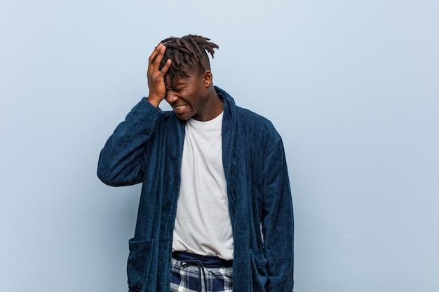 Tragender pyjama des jungen afrikanischen schwarzen mannes, der etwas vergisst, stirn mit palme schlägt und augen schließt.