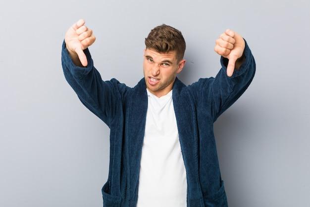 Tragender pyjama des jungen kaukasischen mannes, der unten daumen zeigt und abneigung ausdrückt.