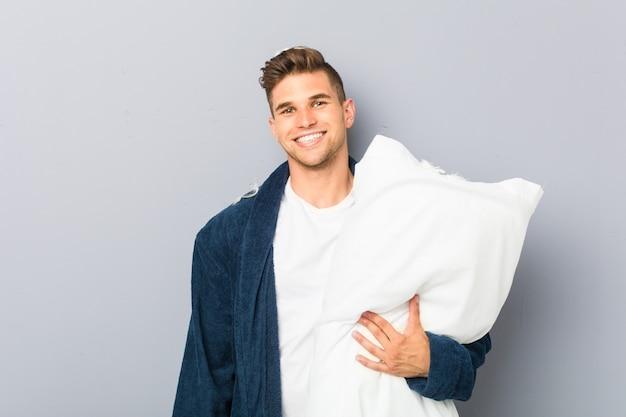 Tragender pyjama des jungen mannes, der ein kissen glücklich, lächelnd und nett hält.