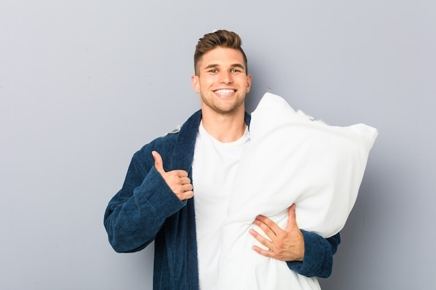 Tragender pyjama des jungen mannes, der ein kissen lächelt und daumen hochhält