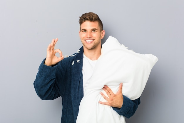 Tragender pyjama des jungen mannes, der ein kissen nett und überzeugt hält, okaygeste zeigend.