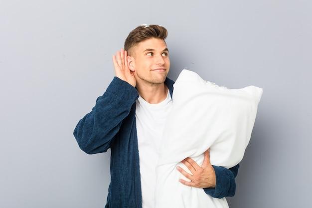 Tragender pyjama des jungen mannes, der ein kissen versucht, einen klatsch zu hören hält.