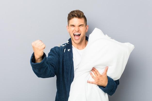 Tragender pyjama des jungen mannes, der ein kissen zujubelt sorglos und aufgeregt hält. sieg-konzept.