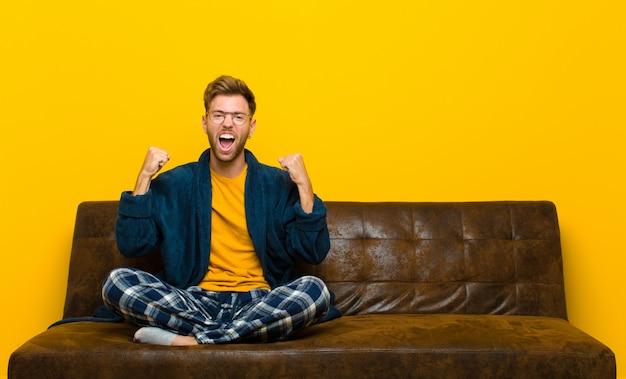 Tragender pyjama des jungen mannes, der glücklich, positiv und erfolgreich sich fühlt und sieg, leistungen oder viel glück feiert. auf einem sofa sitzen