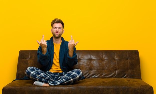 Tragender pyjama des jungen mannes, der provozierend, konkurrenzfähig und obszön sich fühlt und den mittelfinger, mit einer rebellischen haltung leicht schlägt