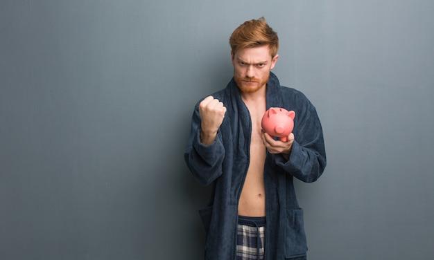Tragender pyjama des jungen rothaarigemannes, der der front die faust, verärgerten ausdruck zeigt. er hält ein sparschwein.