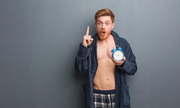 Tragender pyjama des jungen rothaarigemannes, der eine großartige idee, konzept der kreativität hat. er hält einen wecker.