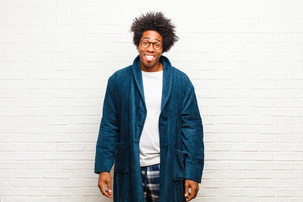 Tragender pyjama des jungen schwarzen mannes mit dem kleid, das angewidert und gereizt sich fühlt, zunge heraus haftet und etwas böses und yucky ablehnt