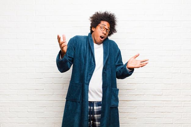 Tragender pyjama des jungen schwarzen mannes mit dem kleid, das mit einem stummen, verrückten, verwirrten, verwirrten ausdruck zuckt und gegen ziegelstein gestört und ahnungslos sich fühlt