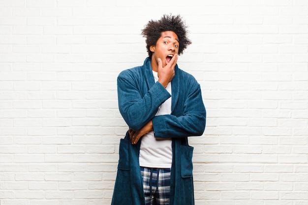 Tragender pyjama des jungen schwarzen mannes mit dem kleid mit offenem mund im schock und im unglauben, wenn die hand auf backe und arm gekreuzt ist, gefühl betäubt und gegen backsteinmauer überrascht