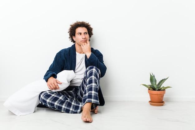 Tragender pyjama des reifen mannes, der auf dem hausboden seitlich schaut mit zweifelhaftem und skeptischem ausdruck sitzt.