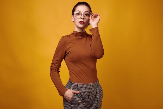 Tragender rollkragenpullover und gläser der mode brunette-frau auf gelbem hintergrund
