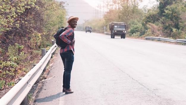 Tragender rucksack der afrikanischen mannreise, der auf der autobahn straße geht konzept des tourismus-tages