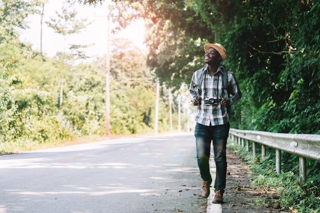 Tragender rucksack der afrikanischen mannreise, der auf der autobahn straße geht