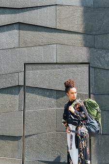 Tragender rucksack der stilvollen frau, der weg draußen betrachtet