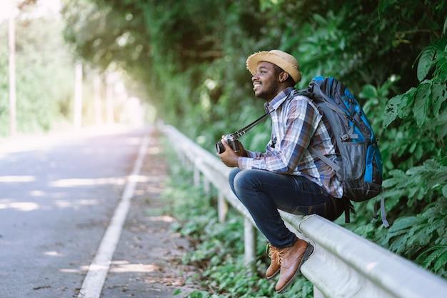 Tragender rucksack des afrikanischen mannreisenden und halten der kameraseite die landstraßenstraße