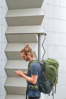 Tragender rucksack des jungen modernen männlichen reisenden unter verwendung des mobiltelefons an draußen