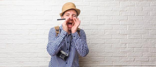Tragender rucksack des jungen reisenden und eine weinlesekamera, die glücklich, überrascht durch ein angebot oder eine förderung schreit, klaffend, springend und stolz. eine kreditkarte halten.