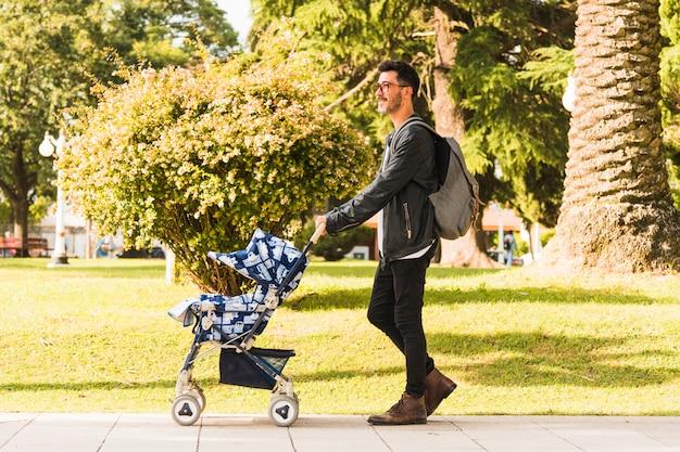 Tragender rucksack des stilvollen mannes, der mit kinderwagen im park geht