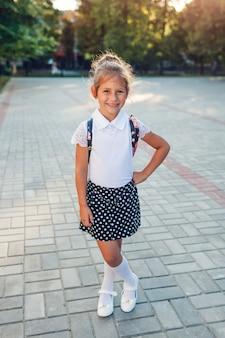 Tragender rucksack und schuluniform des glücklichen schülermädchens. scherzen sie das betrachten der kamera, die draußen grundschule steht.