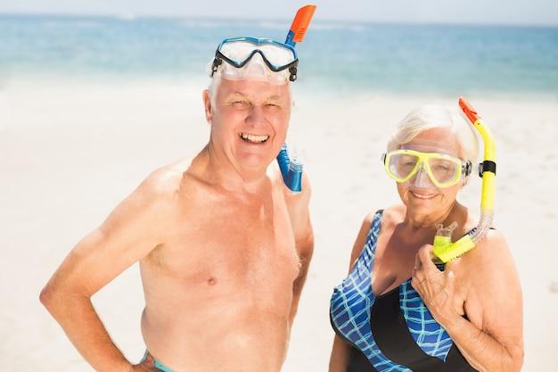 Tragender schnorchel der älteren paare und taucherbrille