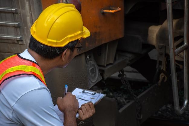 Tragender schutzhelm des asiatischen ingenieurs mit der prüfung des zugs auf wartung