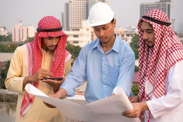 Tragender schutzhelm des geschäftsmannes und des ingenieurs mit zwei arabern, der papier hält