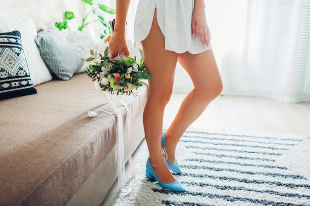 Tragender silk hausmantel der braut und blaue schuhe und blumenstrauß zu hause halten. hochzeitstag