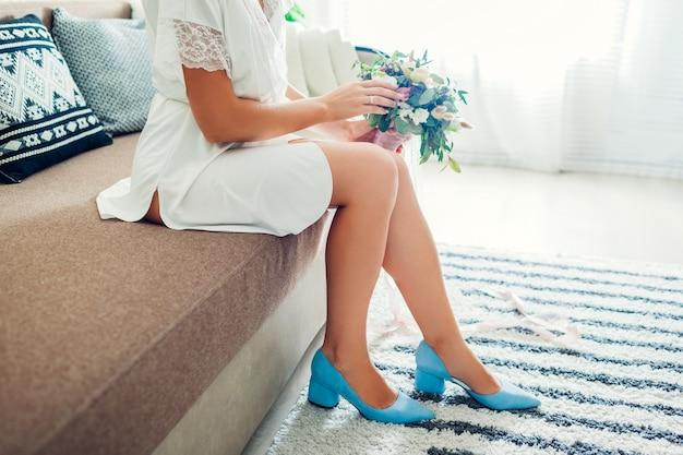 Tragender silk hausmantel der jungen braut und blaue schuhe und blumenstrauß zu hause halten. hochzeitstag