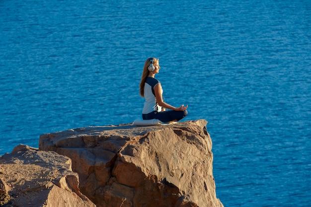 Tragender sportanzug und kopfhörer der frau, die in lotus position auf felsen über dem meer, meditierend sitzen, hören musik. yoga im freien.
