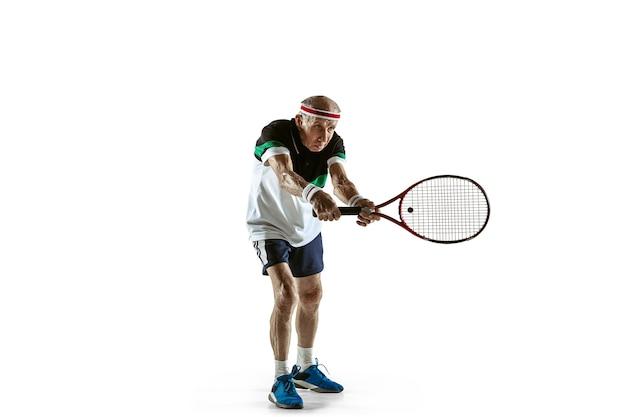 Tragender sportkleidung des älteren mannes, der tennis lokalisiert auf weißem hintergrund spielt. kaukasisches männliches model in toller form bleibt aktiv und sportlich. konzept von sport, aktivität, bewegung, wohlbefinden. exemplar, anzeige.