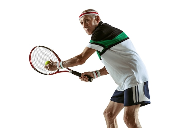 Tragender sportkleidung des älteren mannes, der tennis lokalisiert auf weißer wand spielt. kaukasisches männliches model in toller form bleibt aktiv und sportlich. konzept von sport, aktivität, bewegung, wohlbefinden. exemplar, anzeige.