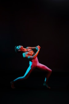 Tragender trikotanzug des emotionalen balletttänzers, der im scheinwerfer durchführt