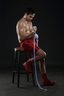 Tragender weißer bügel des jungen asiatischen boxermannes